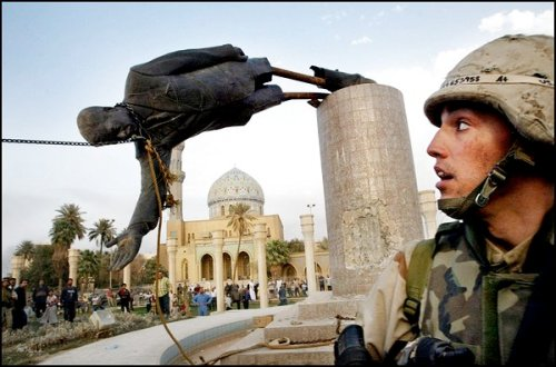 A U.S. SOLDIER WATCHES A STATUE OF PRESIDENT SADDAM HUSSEIN FALL IN CENTRAL BAGHDAD